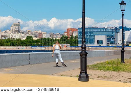 St. Petersburg, Russia - July 03,  2020: Tanned Girl In A White T-shirt And Blue Jeans Roller-skates