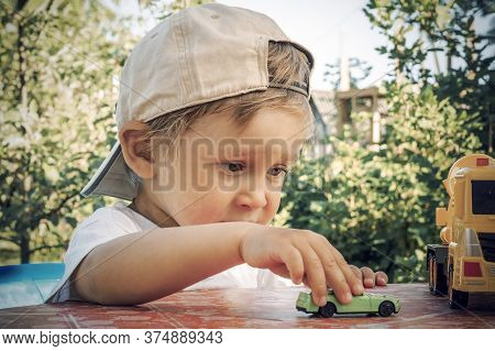A Two Year Old Boy Rolls A Small Toy Car On A Table Outdoors. A Child Plays With Small Cars On A Sum