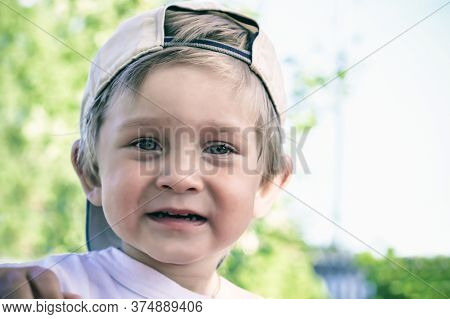 Portrait Of A Beautiful Two Year Old Baby In A Baseball Cap. A Boy With Blond Hair Is Looking At The