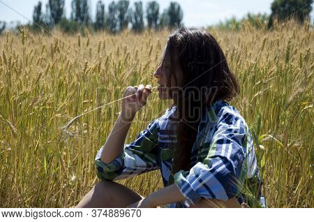Girl In Field With Spikelet. Relax And Think. Beauty And Health. Woman Has Long Healthy Hair. Dry An