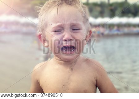 Portrait Of A Crying Baby 1-2 Years Old. Beautiful Baby Crying On The Beach. Toned.