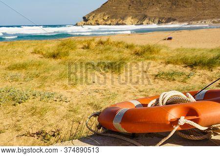 Rescue Red Lifebuoy, Life Preserver Saver Ring On Beach