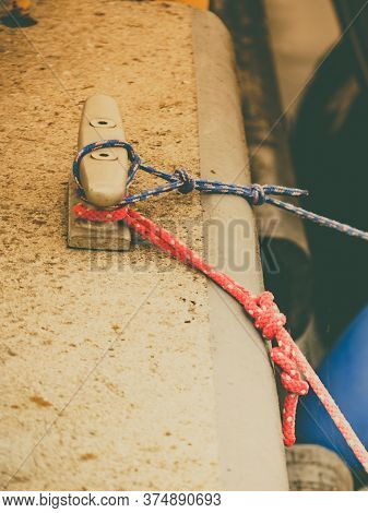 Sailboat Yacht Detailed Parts, Close Up On Metal Cleat With Blue Line Rope Tied Around It. Yachting.