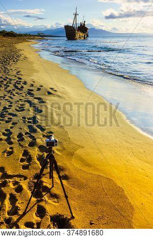 Professional Camera On Tripod Taking Picture Film Video From Greek Coastline With Rusty Shipwreck Di