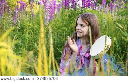 10 Year Old Girl With Long Hair Sits In A Clearing With Lupine Flowers And Plays With A Tambourine