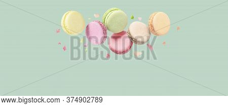 French Macaroons In Pastel Colors Falls Mixed With Crumbs On Mint Background.