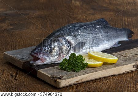Closeup Of Bass With Lemon On Wood