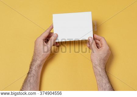 Male Hands Holding A Small Box In Front Of Yellow Background, Mock-up Series Template Ready For Your