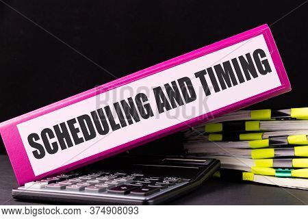 Scheduling And Miting Text Is Written On A Folder Lying On A Stack Of Papers On An Office Desk. Busi