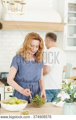 Vertical Waist Up Portrait Of Elegant Mature Woman Mixing Salad While Enjoying Cooking In Kitchen Wi