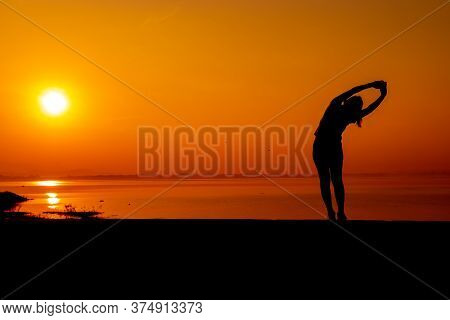 Silhouette Woman Workout Alone With Sunset Background. Healthy And Solo Exercise Activity. Wellness