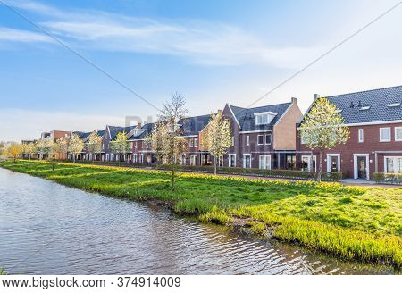 Row Of Modern Houses In A Family Friendly Suburban Neighborhood With Blooming Daffodils In Veenendaa