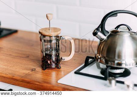 Loose Hibiscus Tea In French Press. Metallic Teapot On The Gas Oven. Bright Kitchen Interior. White