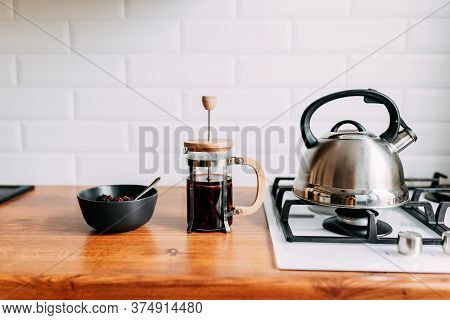 Loose Hibiscus Tea And Hot Water. Metallic Teapot On The Gas Oven. Bright Kitchen Interior. White Mo
