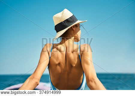 Rear View Woman On The Beach In Straw Hat