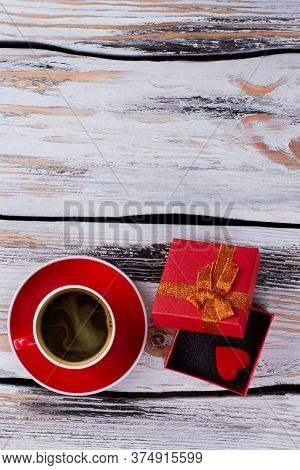 Topview Red Cup Of Coffee And Opened Gift Box. Old White Wooden Background.