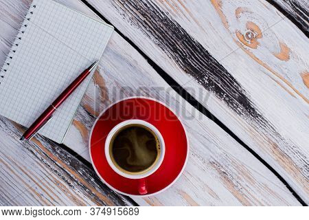 Topview Empty Ceramic Cup And Notepad With A Pen. White Wooden Background.