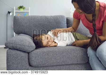 Happy Young Mother Watching Her Daughter Sleep On Sofa In Living Room. Parent Admiring Her Napping K