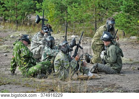 Open-air Paintball Tournament At The End Of Summer In Nature, People In Camouflage, With Paintball G