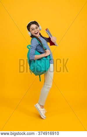 Music School. Happy Girl Back To School. Schoolchild Carry Backpack Yellow Background. School And Ed