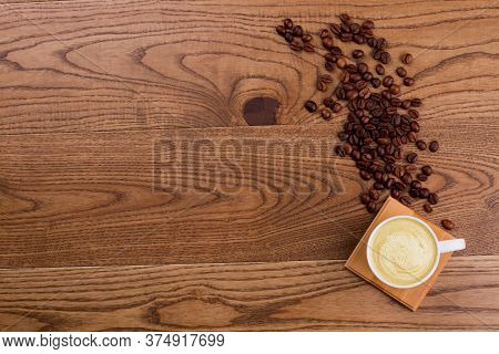 Cup Of Cappuccino Or Latte And Spilled Coffee Beans. Brown Rustic Wooden Background. Topview Flat La