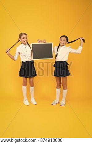 Healthier Hair From Root To Tip. Cute Small Children With Plaited Hair Holding Blackboard On Yellow