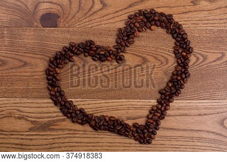Heart Made Of Coffee Beans On Brown Wooden Table. Topview The Symbol Of Love.