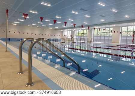 Indoor Swimming Pool Full Of Water With Ladder On The Side.