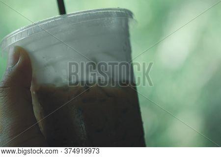 Iced Mocha Coffee In Takeaway Glass And Milk Foam On Hand