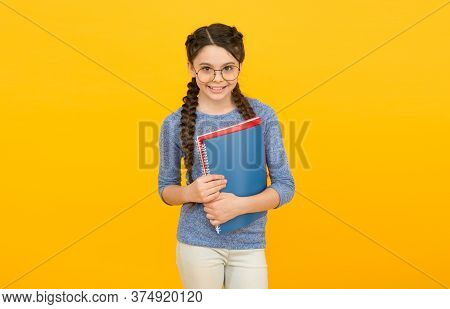 Literature And Creativity. Happy Kid Study Literature At School. Little Girl Hold Books Yellow Backg