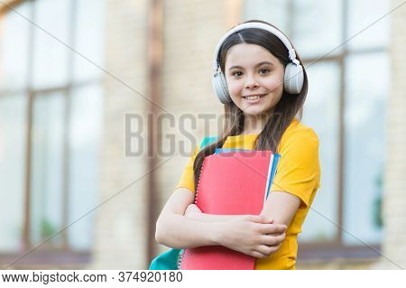 Learning Foreign Language. Small Girl Learn English. Little Child Hold English Books. Listening Comp