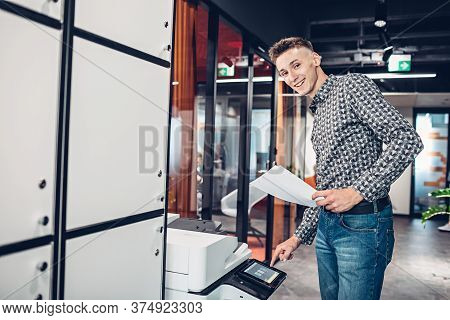 Young Man Office Worker Making Copies Of Documents Using Photocopier