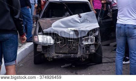 Blurred Image Of A Car Crashed In An Accident. A Crowd Of People Near A Wrecked Car. Soft Focus