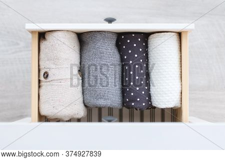 Warm Knitted Clothing In Shades Of Gray And White Is Neatly Folded In A Drawer Of A Wooden Chest Of