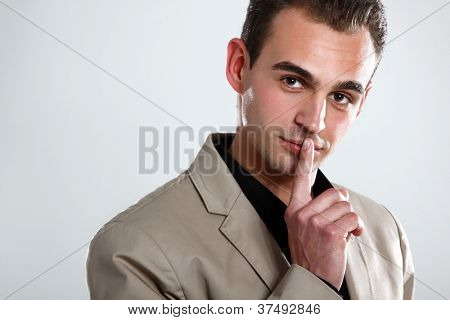 Trendy man in black shirt and beige jacket holding hand near face, portrait of sexy fashion boy looking at camera, isolated