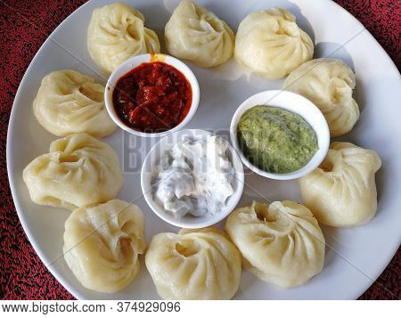 Steamed Nepali Traditional Momos Dumplings Are Served With Different Sauces. Close Up, Side View