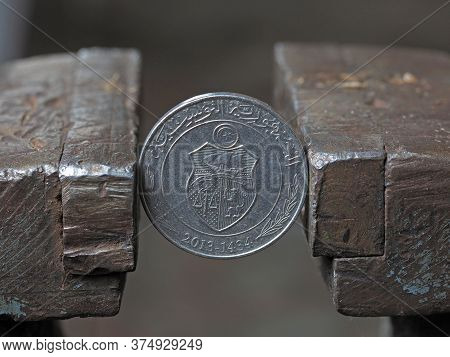 Coin One Tunisian Dinar, Clamped In A Metal Vise, Close-up. Concept Of Financial Problems And Crisis