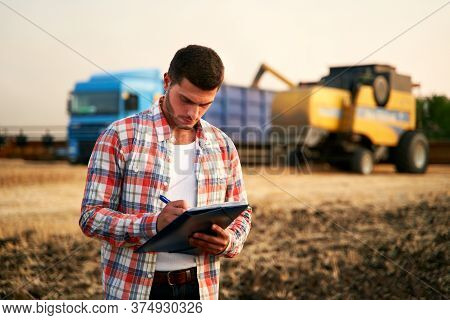 Farmer Controls Loading Wheat From Harvester To Grain Truck. Driver Holding Clipboard, Keeping Notes