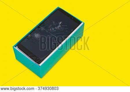 A Smartphone With A Broken Screen In A Gift Blue Box Isolated On A Yellow Background, A Defective Sm