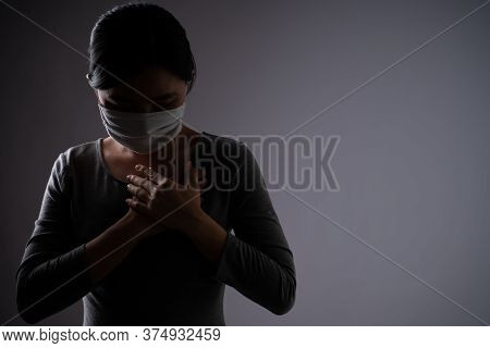 Asian Woman Wearing Protective Face Mask Was Sick With Chest Pain, Putting Her Hands On Her Chest An