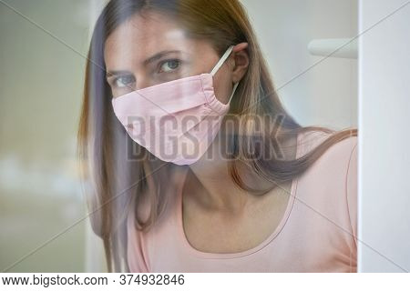 Young Woman In Pink Cotton Face Virus Mask Standing Behind Window Glass Pane, Touching It With Hand,