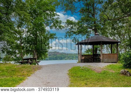 Beautiful Summer View Of A Calm Resting Place With A Wooden Patio By The Sea With Trees And Blue Sky