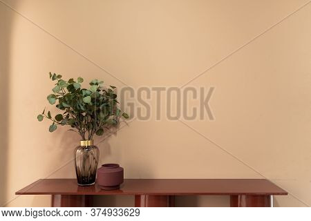 Nice Artificial Plant In Glass Vase With Red Ceramic Vase Setting On Empty Red Table In Minimal Mode