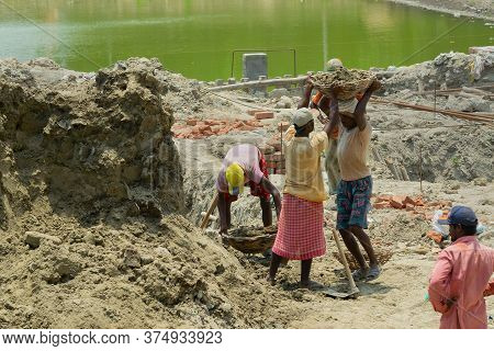 Howrah, West Bengal, India - 7th May 2017 : Indian Male Workers Digging And Carrying Out Soil At Bul