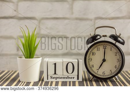 September 10 On A Wooden Calendar Next To The Alarm Clock.september Day, Empty Space For Text.calend