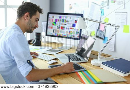 Portrait Of Young Designer Sitting At Graphic Studio In Front Of Laptop And Computer While Working O