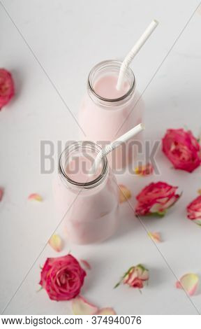 Moon Milk Prepares With Pink Rose Flower In Two Bottles On A White Background. Trendy Relaxing Bedti