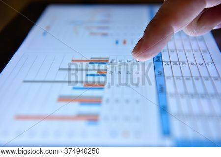 Trader Hand Analyzing At Graph And Checking Business Plan On Tablet Screen. Investment And Financial