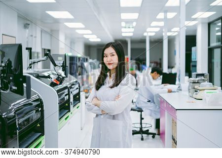 Young Smiling Scientist In White Lab Coat Standing With Automation Blood Analyzer At Medical Laborat