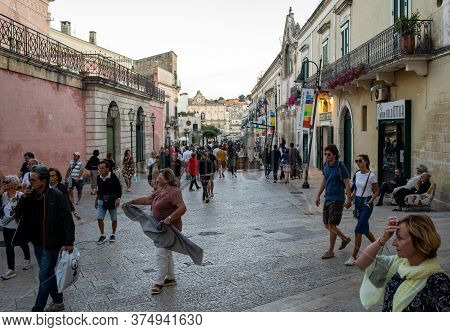 Matera, Italy - September 14, 2019: Tourists During A Walk On Cobblestone Street In The Sassi Di Mat